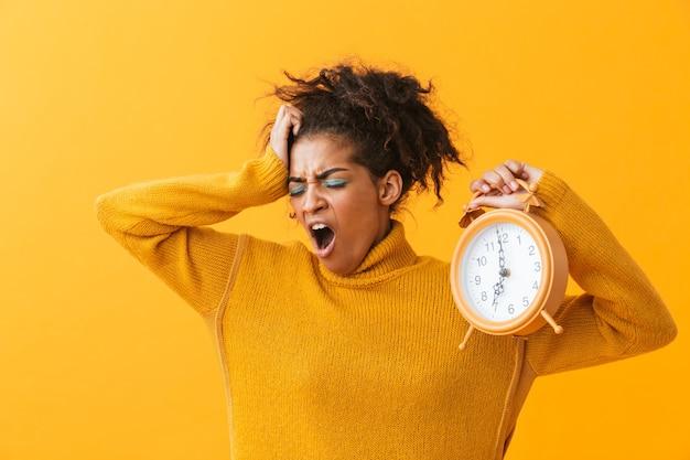 Unglückliche frau des afroamerikaners in der freizeitkleidung, die gähnt, während wecker gehalten, lokalisiert