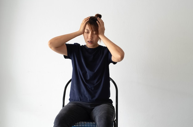 Unglückliche frau, die an der wand sitzt, hände heben kopf berühren, nervös, verärgert und stress