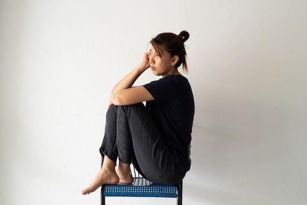Unglückliche frau, die an der wand sitzt, verärgert und gestresst