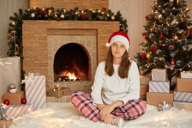 Unglückliche frau, die im wohnzimmer mit weihnachtsdekoration sitzt, schaut mit traurigem blick in die kamera, hält die beine gekreuzt und trägt einen festlichen roten hut, einen weißen freizeitpullover und eine karierte hose.