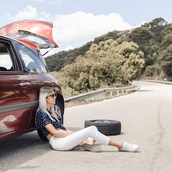 Unglückliche frau, die nahe dem aufgegliederten auto auf kurvenreicher straße sitzt
