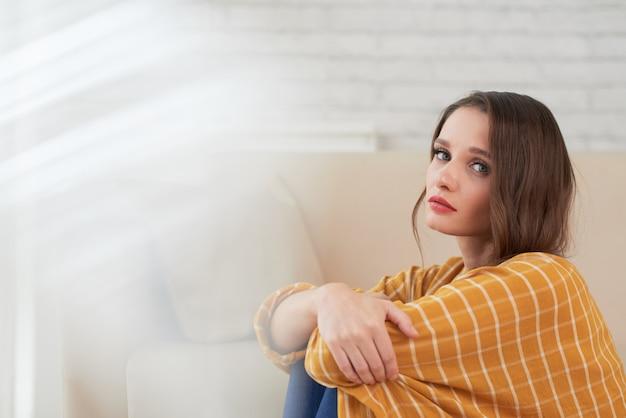 Unglückliche frau in der depressiven stimmung, die zu hause sitzt