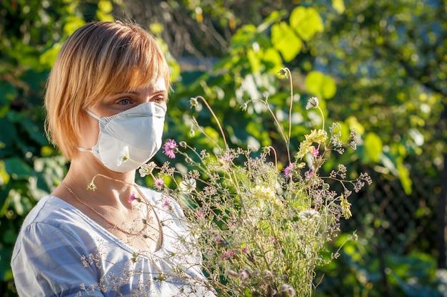 Unglückliche frau in schutzmaske, die einen strauß wildblumen hält und versucht, allergien gegen pollen zu bekämpfen. frau, die ihre nase vor allergenen schützt. allergie-konzept.