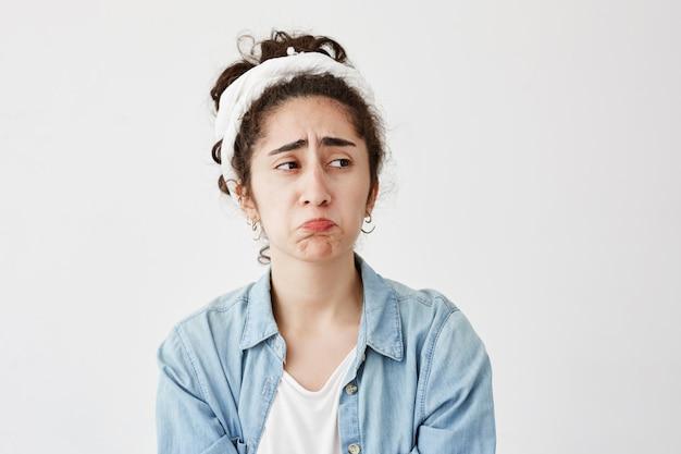 Unglückliche frau mit dunklen und welligen haaren schmollenden lippen, die nach dem streit mit ihrem freund traurig sind, runzelt unzufrieden die stirn, isoliert gegen die weiße wand. konzept der menschlichen negativen emotionen