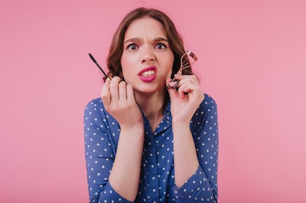 Unglückliche frau mit welligem haar, die ihr make-up vor dem datum macht. nervöses mädchen in blauer kleidung kräuselt wimpern auf rosa wand.
