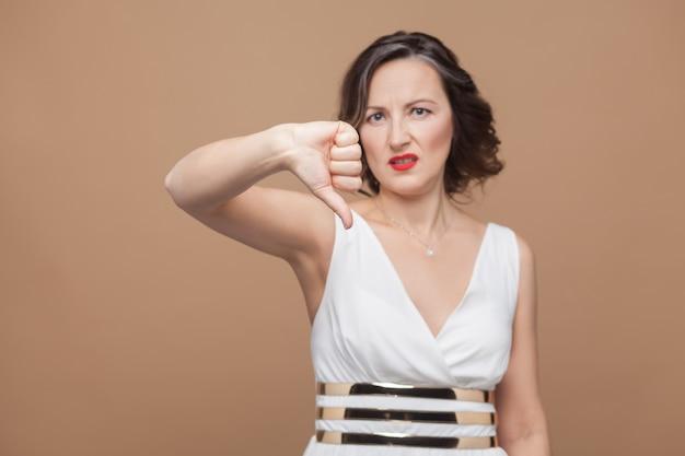 Unglückliche frau mittleren alters, die abneigungszeichen zeigt. emotional ausdrückende frau in weißem kleid, roten lippen und dunkler lockiger frisur. studioaufnahme, drinnen, einzeln auf beigem oder hellbraunem hintergrund