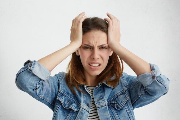 Unglückliche frustrierte frau, die zähne zusammenbeißt, schmerzhaft aussieht, sich verzieht, schläfen drückt, unter migräne oder kopfschmerzen leidet und sich gestresst fühlt