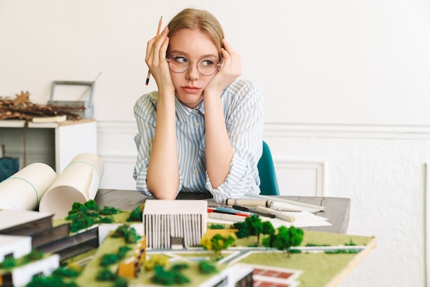 Unglückliche junge architektin in brillen, die entwurf mit hausmodell entwirft und am arbeitsplatz sitzt