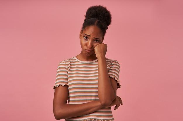 Unglückliche junge braunäugige lockige frau, die ihr gesicht mit erhobener hand hält, während sie traurig nach vorne schaut und weint, während sie über rosa wand posiert