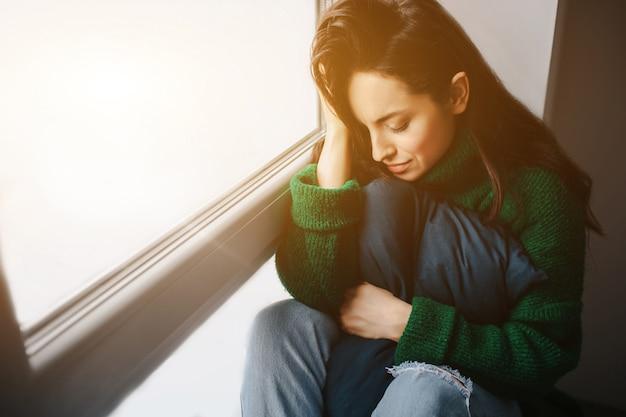 Unglückliche junge frau ist traurig am fenster. die brünette weint. traurigkeit, apathie, depression und melancholie.