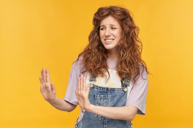 Unglückliche junge ingwerfrau, trägt blaue jeans-overalls und lila t-shirt, schaut mit angewidertem gesichtsausdruck beiseite und zeigt mit beiden händen stoppschild