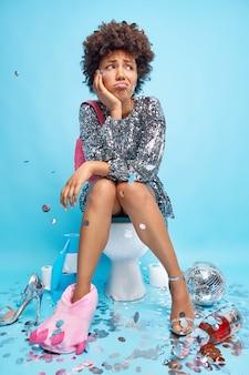 Unglückliche, lockige frau fühlt sich verärgert, nachdem feierposen auf dem toilettenstuhl an durchfall leiden, der von partyattributen umgeben ist, die über blauen wandposen in der toilette des disco-clubs isoliert sind