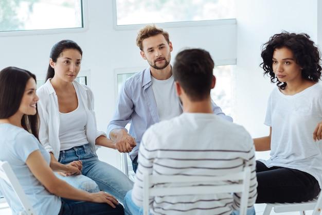 Unglückliche nette junge leute, die den patienten ansehen und seine geschichte hören, während sie an einer psychologischen sitzung teilnehmen