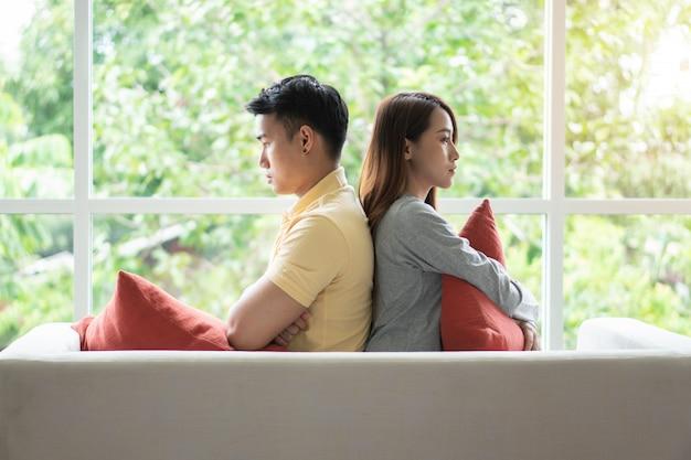 Unglückliche paare, die hintereinander auf der couch sitzen und gespräch vermeiden