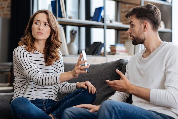 Unglückliche schöne junge frau, die ihr smartphone hält und ihrem freund eine nachricht zeigt, während sie eine erklärung verlangt