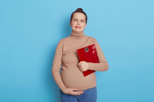 Unglückliche schwangere frau, die eine rote skala lokalisiert auf blau hält