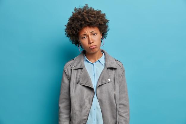 Unglückliche traurige afroamerikanerin neigt den kopf, verärgert über schlechte nachrichten, neigt den kopf, trägt eine graue jacke, sieht düster und gleichgültig aus, steht auf