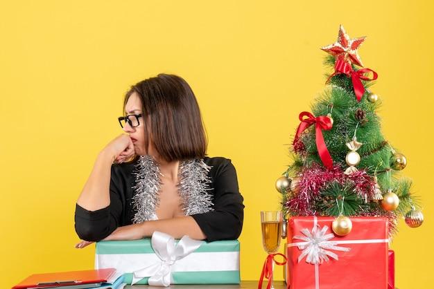 Unglückliche traurige geschäftsdame im anzug mit brille, die ihr geschenk zeigt und an einem tisch mit einem weihnachtsbaum darauf im büro sitzt