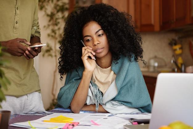 Unglückliche und müde afroamerikanische frau mit lockigem haar, die auf handy spricht