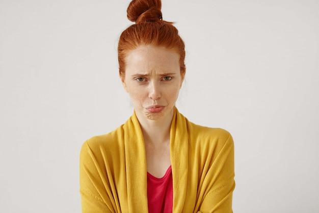 Unglückliche verärgerte rothaarige teenagerin mit einem haarknoten, der beleidigt und enttäuscht aussieht und schmollt, weil sie zu hause bleiben muss, um wegen schlechter noten in der schule geerdet zu sein. menschliche haltung und reaktion
