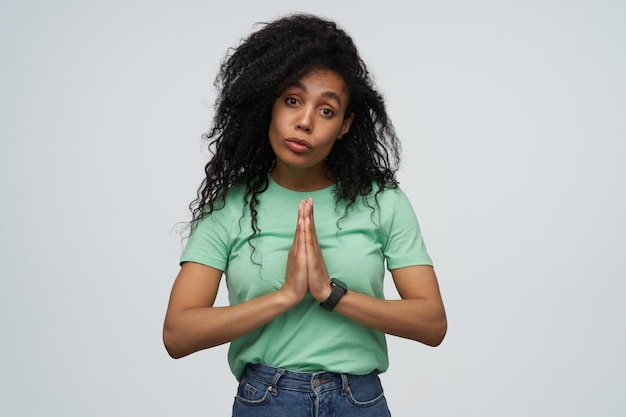 Unglückliche verzweifelte junge frau mit langen lockigen haaren in mint-t-shirt hält die hände in gebetsposition und bittet um hilfe isoliert über grauer wand