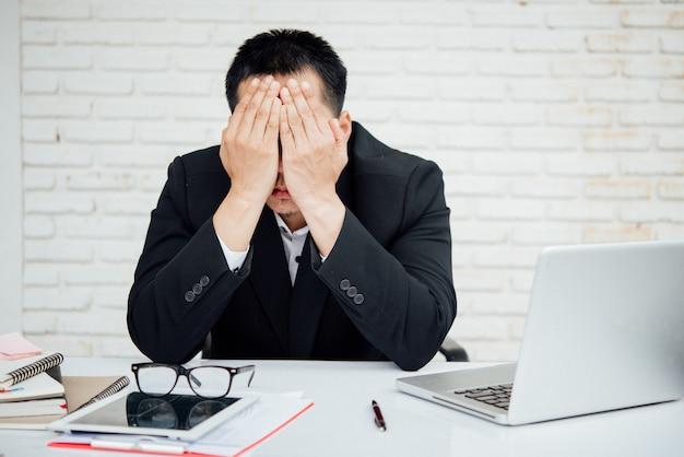 Unglückliche wirtschaftler des geschäftsmannes, die im büro sitzen
