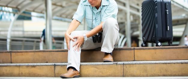 Unglücklicher älterer mann, der unter knieschmerzen leidet. reise- und tourismuskonzept. gesundheitsproblem und personenkonzept.