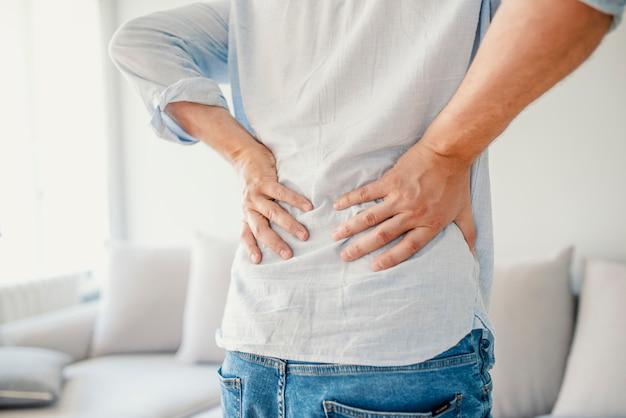 Unglücklicher älterer mann, der zu hause unter schmerz in den hinteren oder zügeln leidet