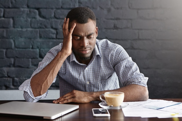 Unglücklicher afrikanischer geschäftsmann, der sich gestresst und frustriert fühlt