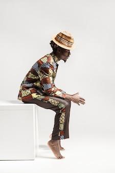 Unglücklicher afro-mann in traditioneller kleidung sitzt auf würfel