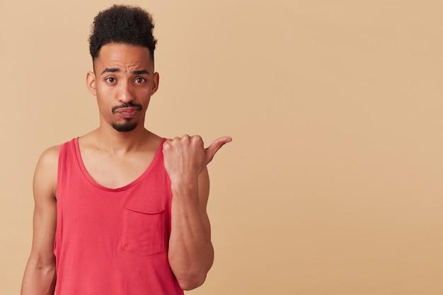Unglücklicher afroamerikaner, bärtiger kerl mit afro-frisur. trage ein rotes trägershirt. zeigt nach rechts auf den kopierbereich, isoliert über der pastellbeigen wand