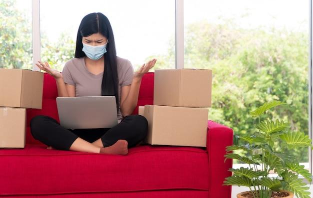 Unglücklicher asiatischer junger unternehmer auf einer maske müder ausdruck und satt von problemen bei der geschäftsabwicklung zu hause