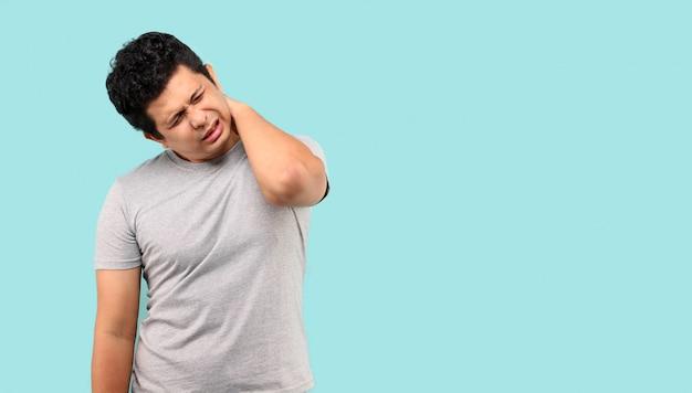 Unglücklicher asiatischer mann, der unter nackenschmerzen auf hellblauem hintergrund im studio leidet