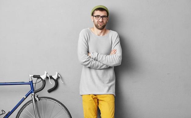 Unglücklicher bärtiger mann, der losen pullover und gelbe hosen trägt und die hände gekreuzt hält, während er fahrrad fährt. junger hipster-student, der auf ausbilder wartet, um fahrradhandhabungsfähigkeiten zu lernen