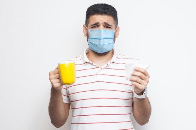 Unglücklicher besorgter kranker mann mit chirurgischer medizinischer maske, der eine gelbe tasse mit weißem gewebe hält und hält, heißen tee trinkt, grippe, kranke oder coronavirus hat. indoor, isoliert, weißer hintergrund, studioaufnahme