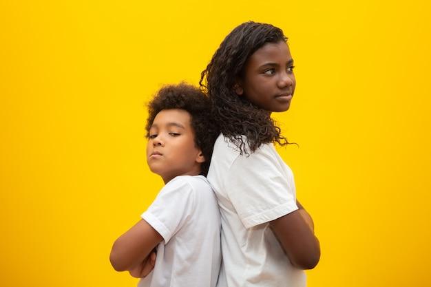 Unglücklicher bruder und schwester. die jungen brüder, die zurück zu rückseite mit den armen stehen, falteten gelb zusammen.