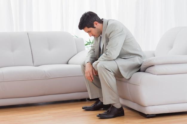 Unglücklicher buinessman, der auf dem sofa senkt seinen kopf sitzt
