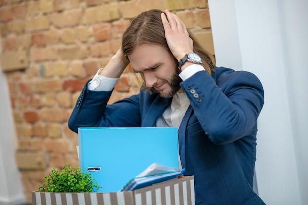 Unglücklicher emotionaler mann im geschäftsanzug mit box, die seinen kopf mit händen drinnen umklammert