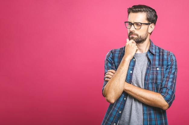 Unglücklicher entschlossener europäischer mann mit borsten, die das kinn berühren, während er mit ernstem und besorgtem blick in die kamera denkt und schaut