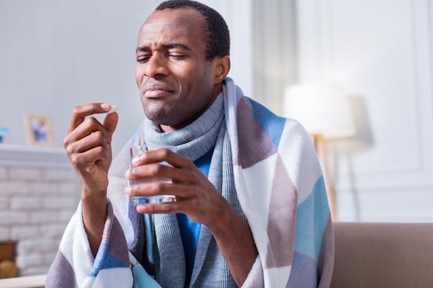 Unglücklicher freudloser kranker mann, der eine pille hält und sie ansieht, ohne sie nehmen zu wollen
