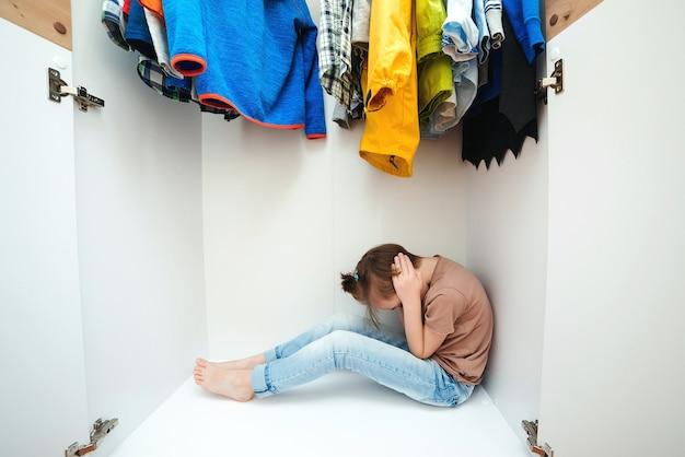 Unglücklicher junge, der sich im kleiderschrank versteckt. häusliche gewalt und missbrauchtes konzept. unglückliche kindheit. verärgertes kind weint in seinem zimmer. kleines kind hat angst.