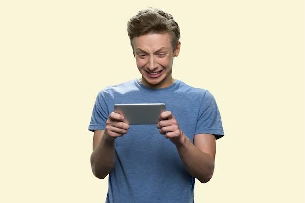 Unglücklicher junge spielt spiel im smartphone