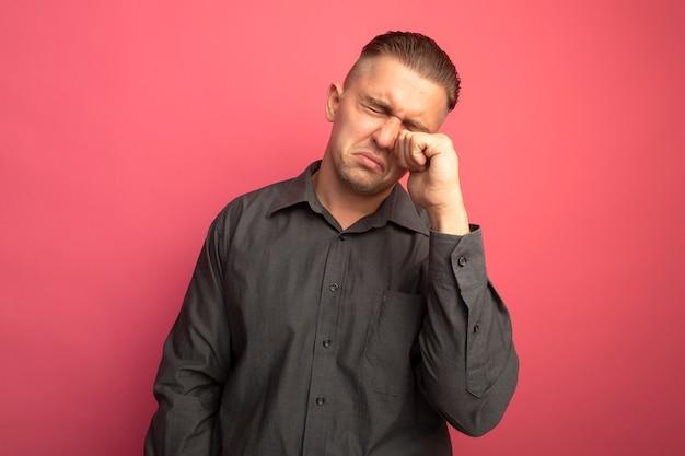 Unglücklicher junger gutaussehender mann im grauen hemd, das seine weinenden augen reibt, die über rosa wand stehen
