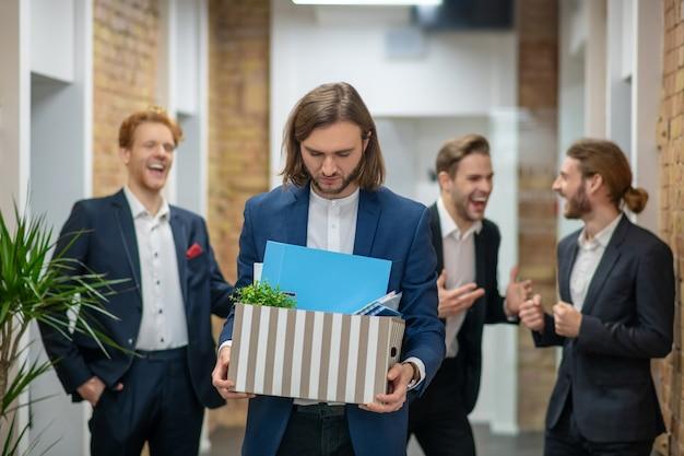 Unglücklicher junger langhaariger mann, der mit kiste und drei fröhlichen angestellten geht, die hinterher lachen