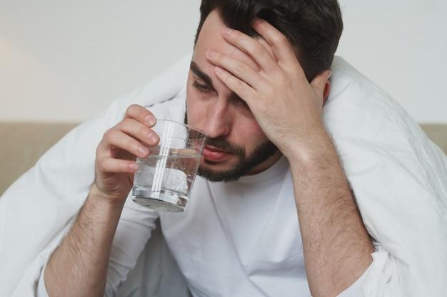 Unglücklicher junger mann mit covid19 oder grippe, der seine stirn berührt und wasser aus glas trinkt, während er während der selbstisolierung zu hause auf dem bett sitzt
