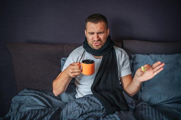 Unglücklicher junger mann sitzt auf bett im schlafzimmer und schaut auf orange tasse. er hält es in einer hand und ein stück zitrone in einer anderen. guy ist unzufrieden. er schrumpft. flüssigkeit in der tasse riecht widerlich.