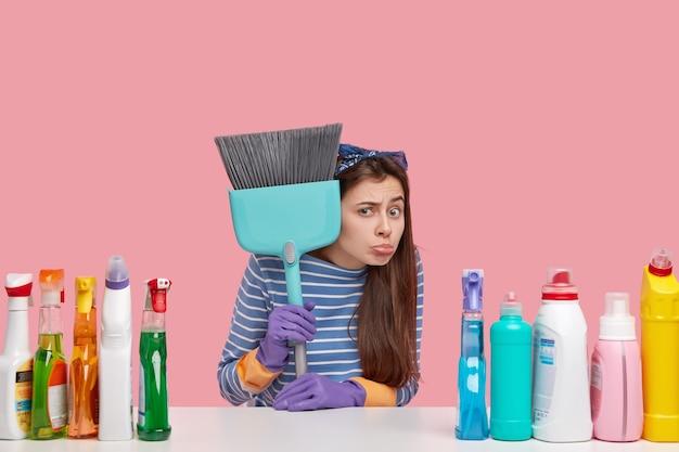 Unglücklicher junger reinigungsdienstmitarbeiter hält besen, verwendet zahlreiche reinigungsmittel, ist nicht bereit zu arbeiten, hat eine negative einstellung zur arbeit