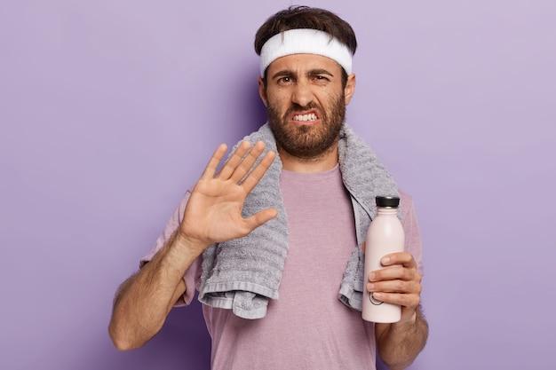 Unglücklicher kaukasischer mann weigert sich, an sportwettkämpfen teilzunehmen, macht ablehnungsgeste, hält flasche wasser, hat cardio-training im fitnessstudio trägt stirnband und t-shirt. ein schluck frische nach dem training