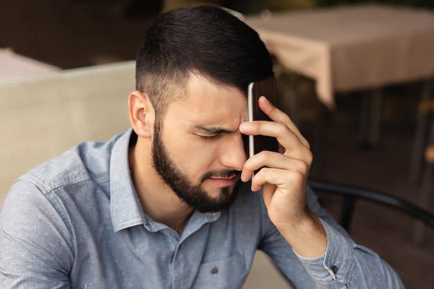 Unglücklicher mann, der ein telefon in der nähe seines kopfes hält. kopfschmerzen von harter arbeit zu hause