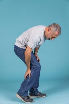 Unglücklicher mann, der unter starken schmerz auf blauer tapete leidet